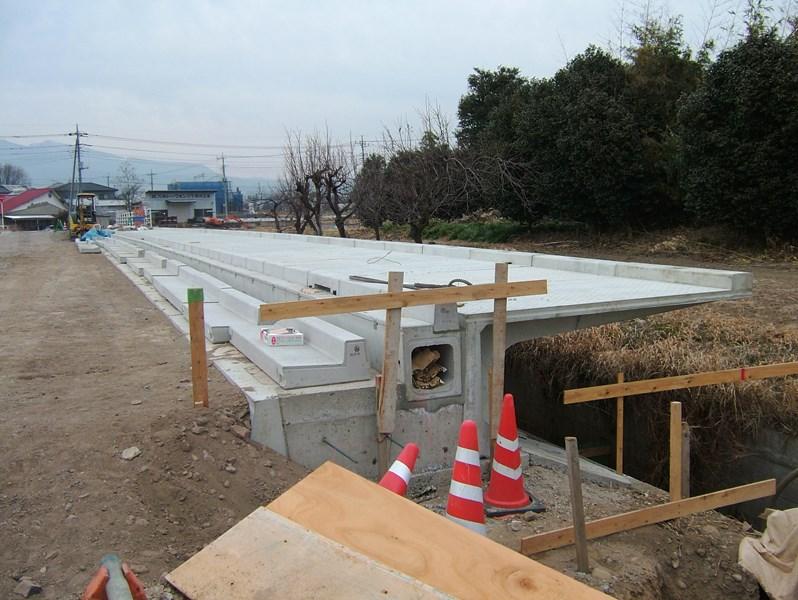 張出歩道のフーチング部に切欠きを設けて側溝を設置した施工例